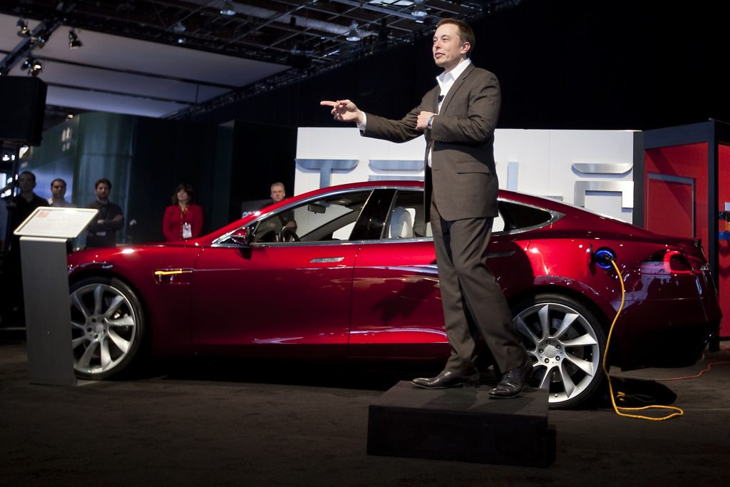 Elon Musk, chairman and chief executive officer of Tesla Motors Inc., speaks in front of a Tesla Model S electric car on day two of the 2010 North American International Auto Show in Detroit, Michigan, U.S., on Tuesday, Jan. 12, 2010. The 2010 Detroit auto show runs through January 24 and features 60 new vehicle premieres. Photographer: Daniel Acker/Bloomberg via Getty Images
